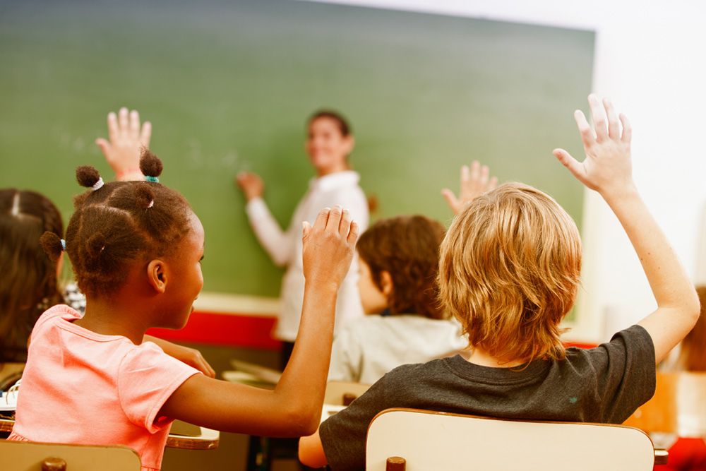 Kids in a classroom raising their hands